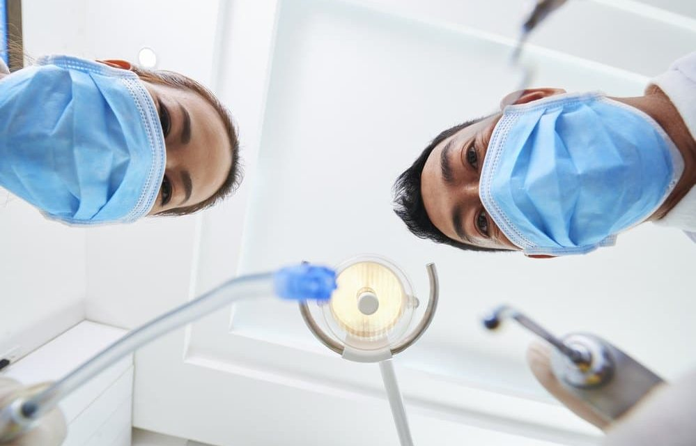 dentists standing over a patient